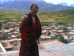 Tibetan monasteries are often, though not always, built on a hill overlooking the town that they serve. Tibetan buildings such as these in the background, usually have earthen roofs which are used for drying hay and crops. Ganzi Lamasery, Sichuan