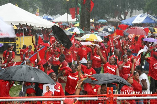 PNM supporters at Woodford Square, Port of Spain, withstand the heavy rains