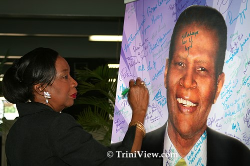 Former Minister of Culture, Joan Yuille Williams signs the picture of Terry Joseph