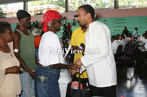 RIGHT: MP for Laventille West, Nileung Hypolite presents Christmas Hampers to the elderly residents