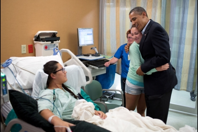 President Barack Obama hugs Stephanie Davies, who helped her friend, Allie Young during the movie theater shootings