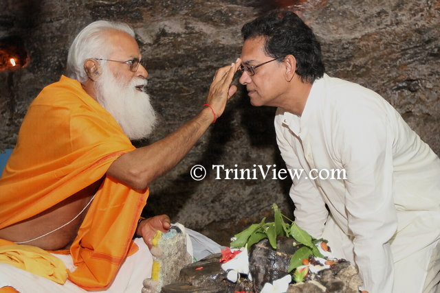 Dr. Vijay Narinesingh bends to receive a blessing from the pundit