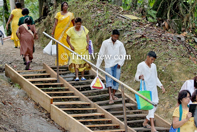 Pilgrims descend makeshift stairs to wthe river