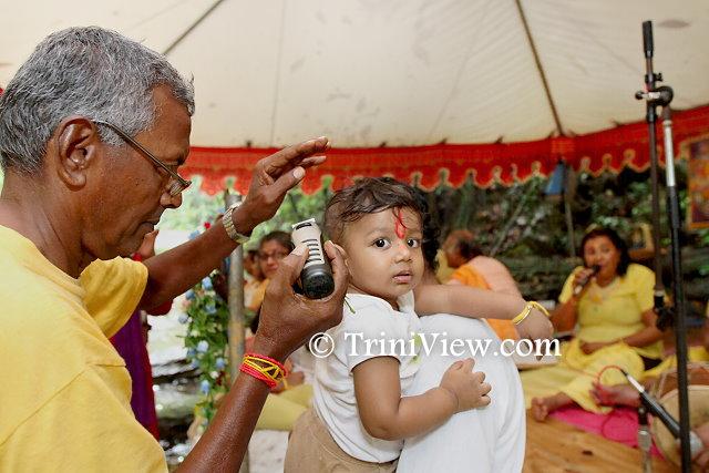 A baby's head is being shaved in the Mundan Sanskaar Ghat