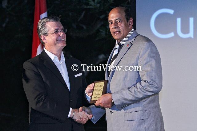 (R) Dr. Tim Goopeesingh accepts a congratulatory plaque from Mr. Robert Sowah