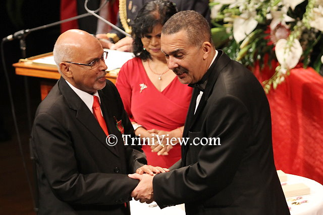 (L) Pastor Clive Dottin receives his Chaconia Medal, Silver