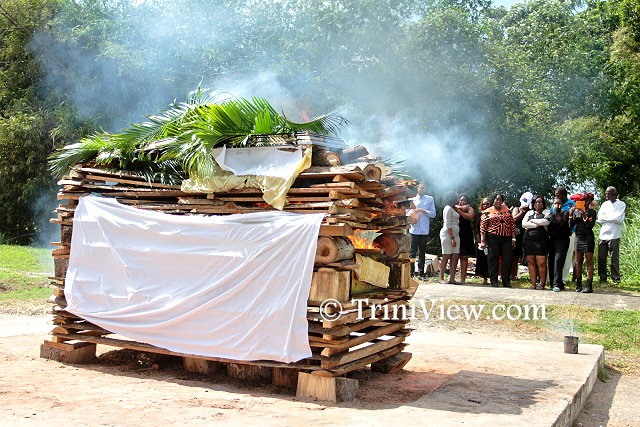 Family and friends watch the cremation of the body of Junior Noel