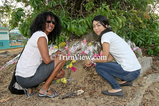 Friends and well-wishers lay flowers around the tree where the memorial service was held for Asami Nagakiya