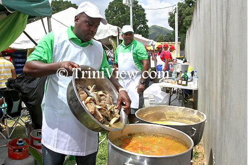 Inter Agency Task Force (IATF) officers (in green) cooking fish broth