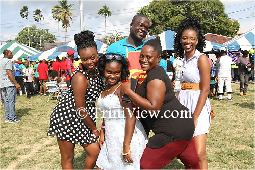 Members of the public enjoy a photo moment with one of the police officers from the Tobago division (back)