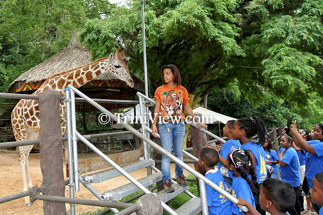 Children checking out one of the Giraffes with a tour guide at the Emperor Valley Zoo