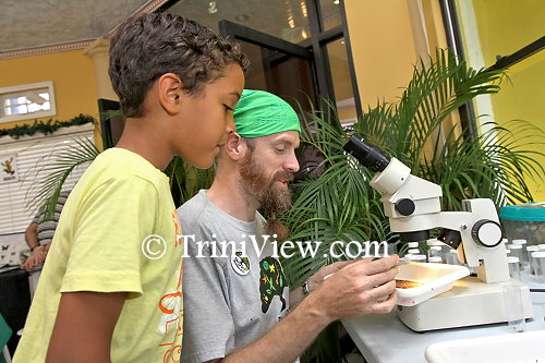 A young curious onlooker observes how Mike Rutherford examines a specimen