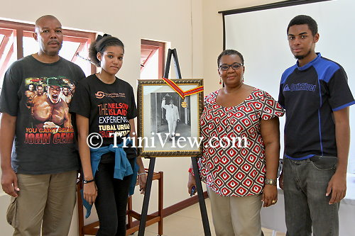 Tubal Uriah 'Buzz' Butler's grandchildren and great-grandchildren pose with an image of him with the Trinity Cross, the nation's highest award at the time which he received in 1970