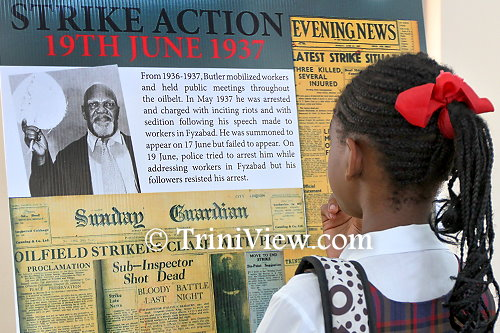 Student reads the exhibited information on the 1930s strikes led by Tubal Uriah 'Buzz' Butler